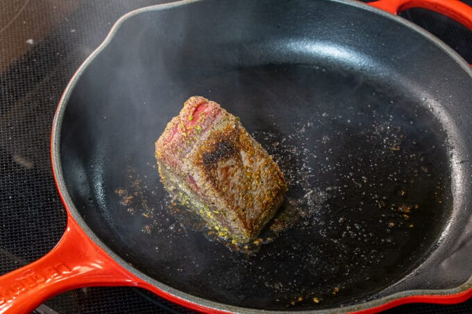 beef being seared in a skillet