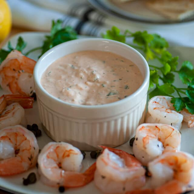 Bowl of seafood sauce with poached shrimp.