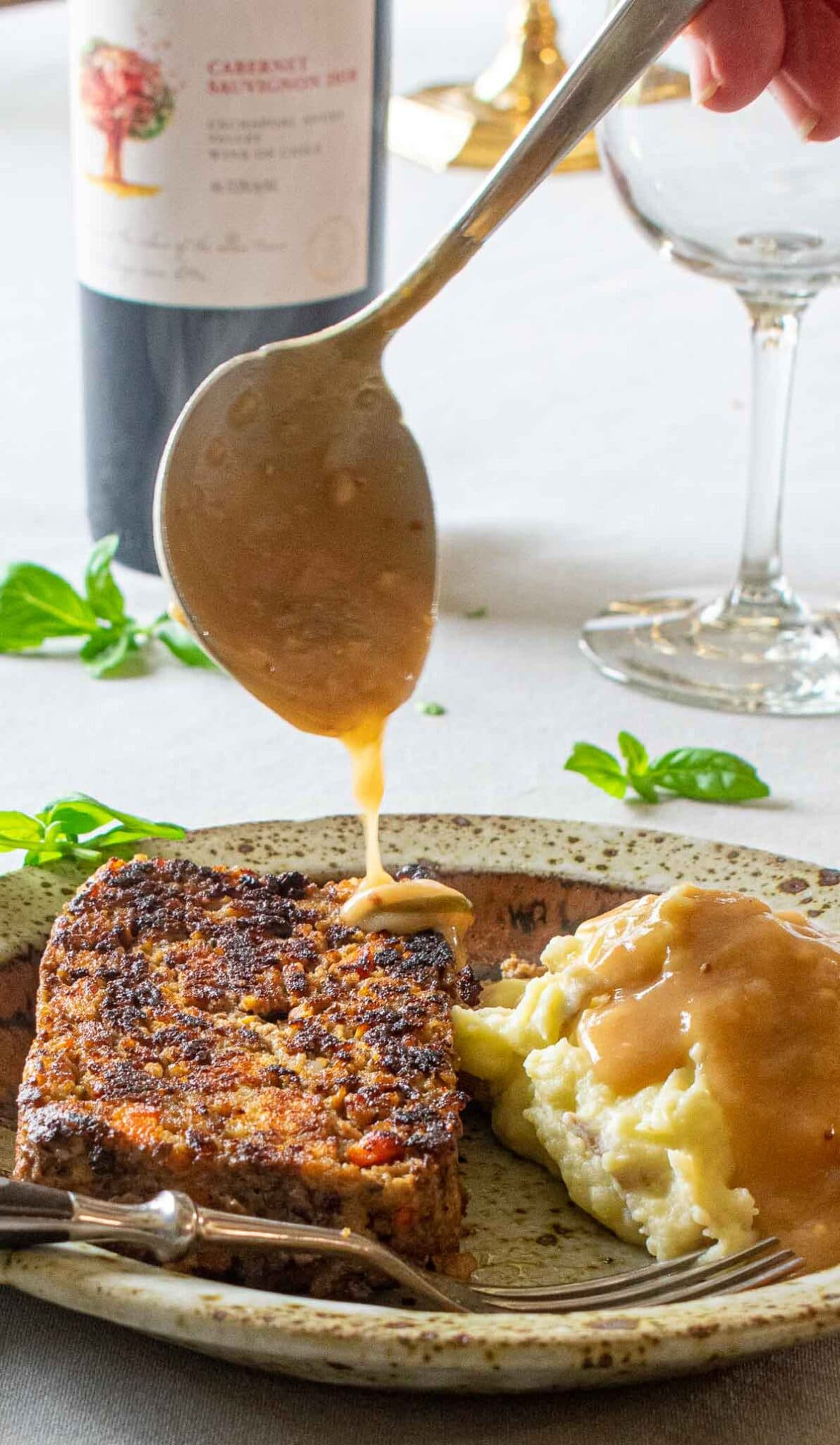 Close up of a ladle of gravy being poured over meatloaf.