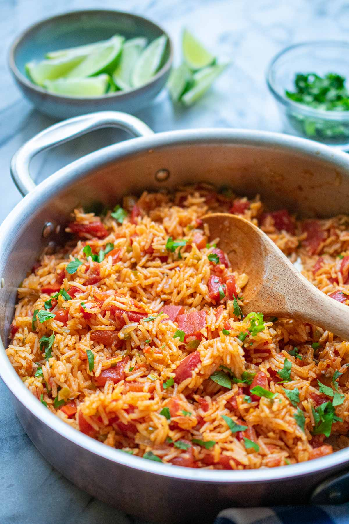 Side view of rice and tomatoes in a skillet with a bowl of lime wedges in the background.