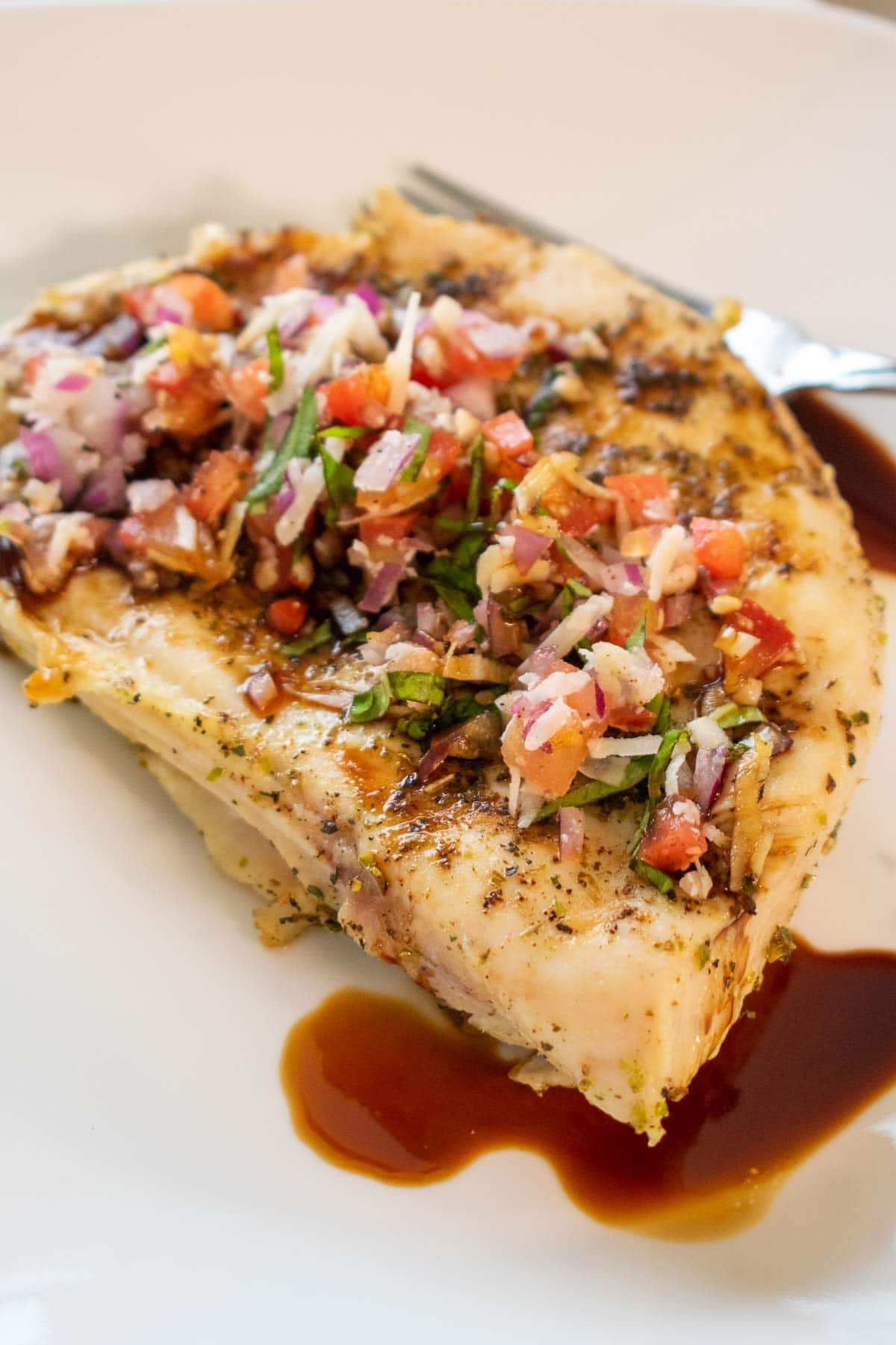 Side view of chicken breast and salsa.