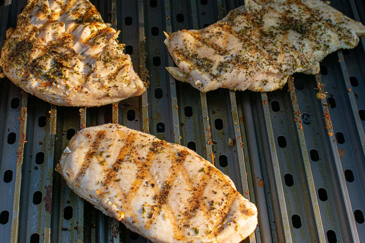 Three chicken breasts on a gas grill.