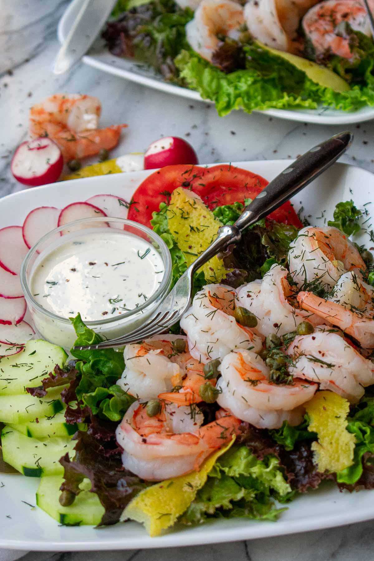 Side view of plated shrimp and dill dressing.