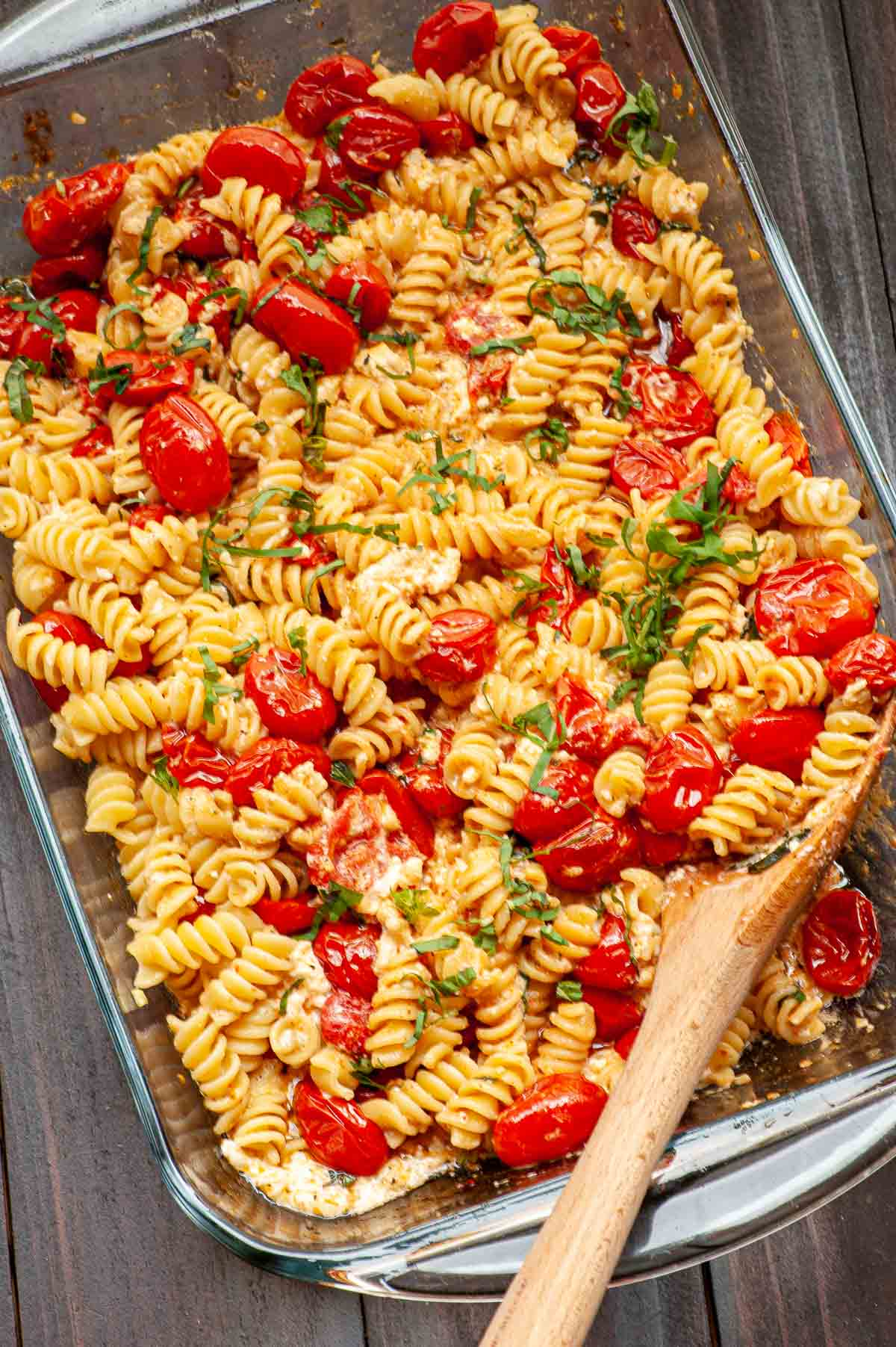 Feta pasta casserole with a wooden spoon for serving.