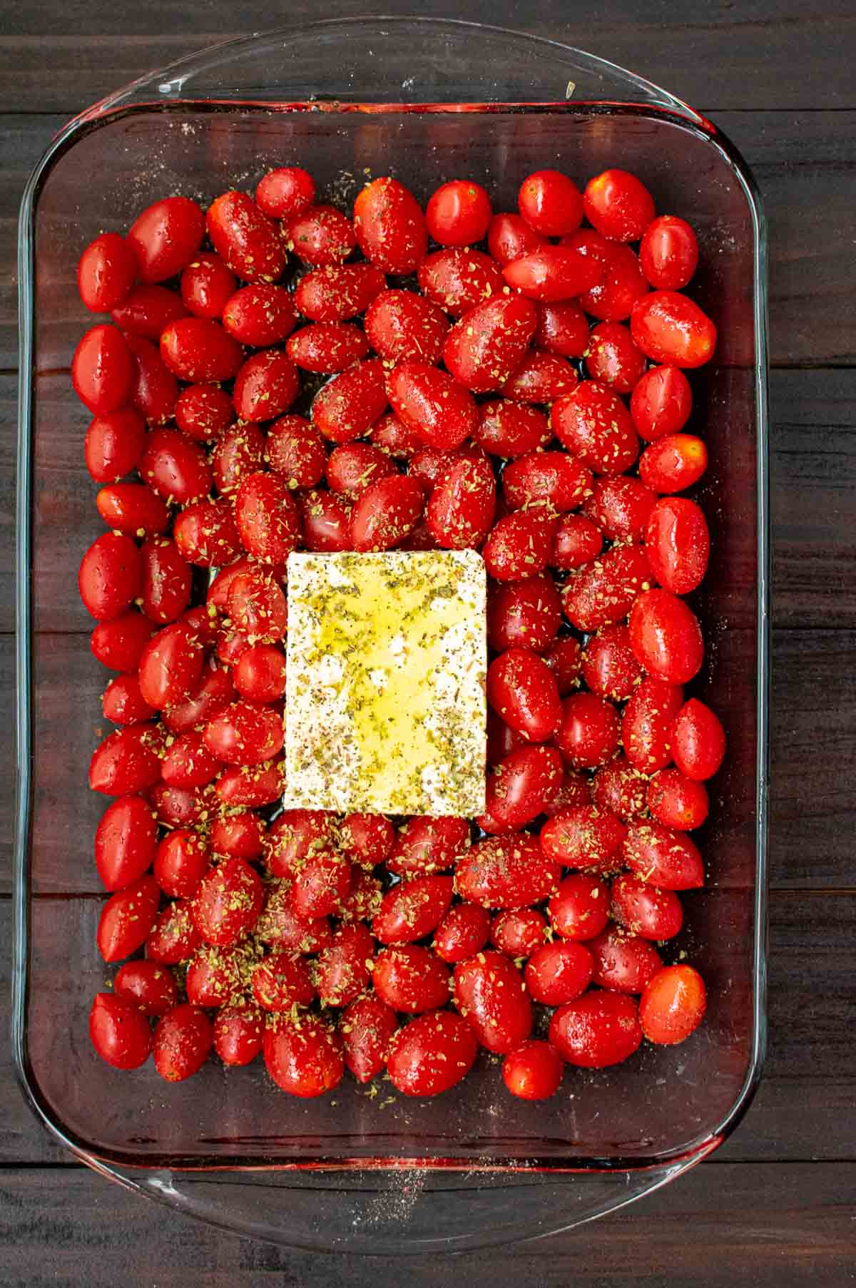 Overhead view of feta cheese and grape tomatoes in the casserole dish.